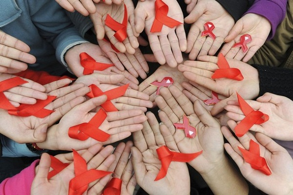 University students hold red ribbons at a photo opportunity during an HIV/AIDS awareness rally on World AIDS day in Chengdu